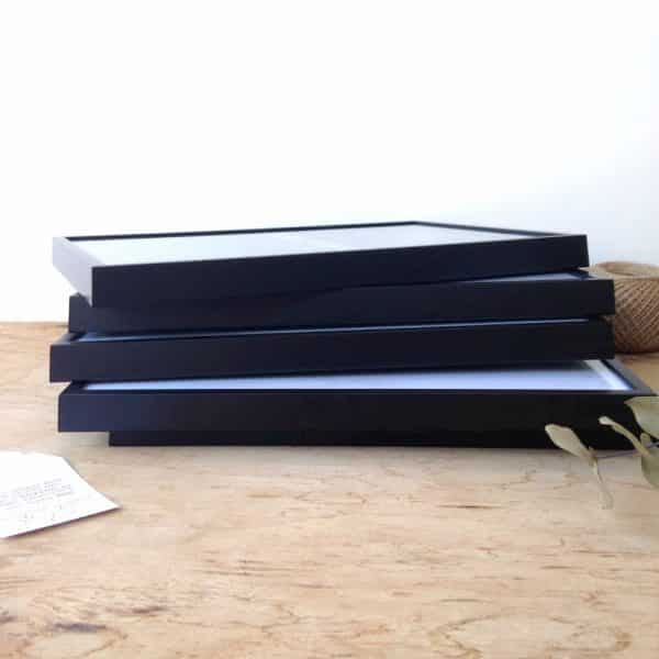 Varios marcos negros apilados de nuestro servicio de enmarcado